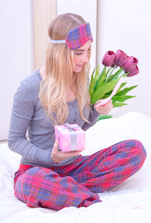 Romantic morning in Valentine day, cute girl receive tulips, gift box and reading greeting card, enjoying relationship, love and romance concept photo