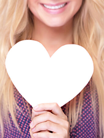 Closeup photo of happy smiling woman holding in hands white paper heart shaped greeting card, healthy lifestyle, romantic Valentine day, love or good health concept photo