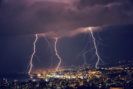 Beautiful lightning at night over gorgeous glowing Lebanon, majestic nighttime cityscape, stormy weather Stockfoto
