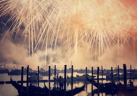 Redentore holiday, Redeemer festival of fireworks, people in gondolas swimming along canal and enjoying majestic salute in the sky, Venice, Italy,
