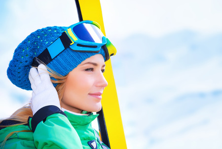 ski mask: Closeup portrait of cute skier girl looking far away, wearing special sportive mask and holding in hands ski equipment, active lifestyle, enjoying winter vacation concept