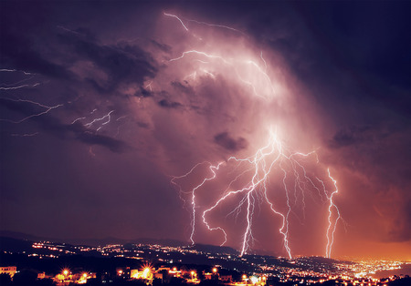 Beautiful lightning over night city, amazing nighttime panorama, powerful bright zipper, stormy weather, power of nature concept