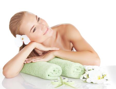 orchidee: Bella donna bionda con dolce fiore di orchidea in capelli isolato su sfondo bianco, godendo day spa, rilassante sulla tabella di massaggio, trattamenti di bellezza medico, benessere stile di vita