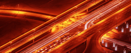 Night roads panoramic background, bird eye view on illuminated highway, modern motorway in Dubai city, UAE photo