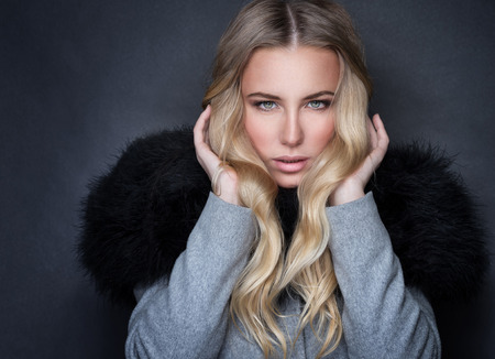 Portrait of beautiful blonde seductive woman on gray background, wearing stylish coat with black fur, sexy look, fashion and beauty lifestyle photo
