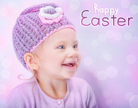 Portrait of happy adorable child wearing cute knitted hat on pink blur background, greeting card with text space, happy Easter holiday photo
