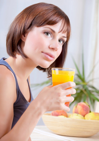 having breakfast: Portrait of a pretty woman holding glass with tasty juice, feamle sitting on the kitchen at home and having fresh peaches for breakfast, healthy eating concept