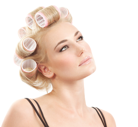 hair curler: Closeup portrait of a beautiful blond female with curlers on hair isolated on white background, making fashionable hairstyle, beauty salon makeover Stock Photo