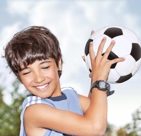Actieve gelukkige jongen in beweging, met plezier buiten, voetballen in sportief zomerkamp, bal te vangen, beste keeper in het voetbal team Stockfoto
