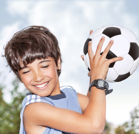 Active happy boy in motion, having fun outdoor, playing football in sportive summer camp, catching ball, best goalkeeper in football team Stock Photo