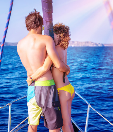 Back side of happy loving couple standing on the mast of luxury sail boat and hugging, enjoying sea view, summer vacation in love photo