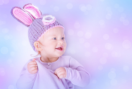 Portrait of happy cute baby girl wearing knitted hat with rabbit ears on purple blur background, beautiful Easter bunny photo
