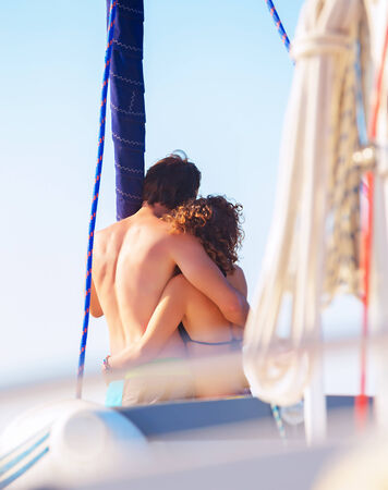 Back side of happy loving couple standing on the mast of luxury sail boat and hugging, enjoying sea view and summer vacation, love concept photo