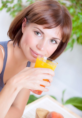 Portrait of beautiful brunette woman drinking tasty fresh juice on at home, having breakfast, organic nutrition, healthy lifestyle concept photo