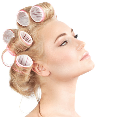 perm: Closeup portrait of beautiful blond woman with curlers on hair isolated on white background, making hairdo, luxury beauty salon