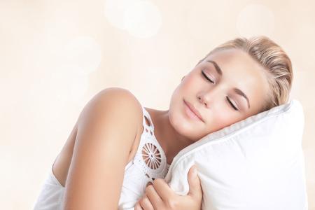 分離された枕で寝ている美しい女性の肖像画ぼかしベージュの背景、幸せな穏やかな日を夢見て、緩和の概念