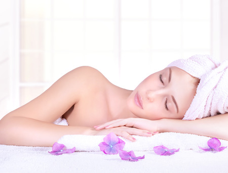 massage table: Beautiful woman with closed eyes lying down on massage table, enjoying day spa, luxury beauty salon, healthy lifestyle Stock Photo