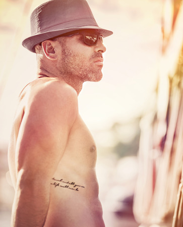 Portrait af a sexy shirtless sailor wearing hat and sunglasses enjoying sunset, man traveling along sea on luxury sailboat, happy summer vacation photo
