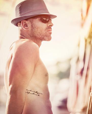 tatouage sexy: Portrait af un marin torse nu sexy avec un chapeau et des lunettes de soleil bénéficiant coucher de soleil, homme de déplacement le long mer sur voilier de luxe, les vacances d'été heureuse Banque d'images