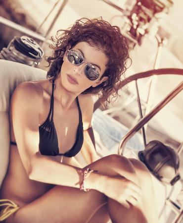 Stylish girl relaxing on sailboat, enjoying mild sunset light, luxury summer vacation, active lifestyle, having fun on sea cruise