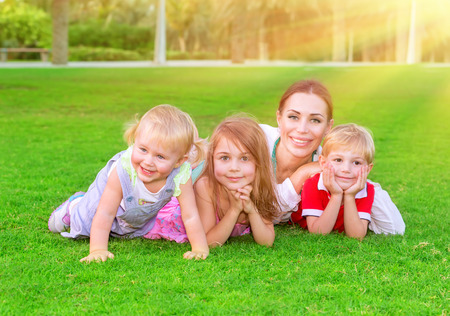 brothers and sisters: Happy family having fun outdoors, beautiful mother with three cute little children lying down on fresh green grass, enjoying spring season