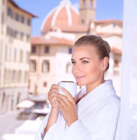 house robe: Portrait of beautiful calm woman drinking coffee in hotel room in Florence, Italy, Europe, standing on balcony on wonderful cityscape background
