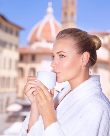 house robes: Portrait of a beautiful calm woman drinking coffee in hotel room in Florence, standing on the balcony and enjoying wonderful cityscape, tourism and travel to Europe,  Italy