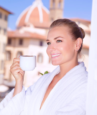 house robes: Portrait of beautiful happy woman drinking coffee in hotel room in Florence, Italy, Europe, standing on balcony on wonderful cityscape background
