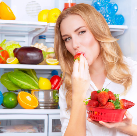Portrait of a beautiful female standing near open fridge full of fresh fruits and vegetables, woman having red ripe juicy strawberry, healthy eating and living  concept