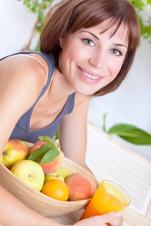 Portrait of beautiful woman eating fresh ripe fruits and drinking juice at home, loss weight, dieting and healthy nutrition concept photo