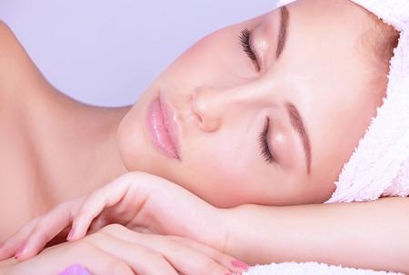 Közeli portré gyönyörű nő csukott szemmel fekve a masszázs asztalra, élvezve day spa, egészséges életmód, orvosi kozmetika Stock fotó