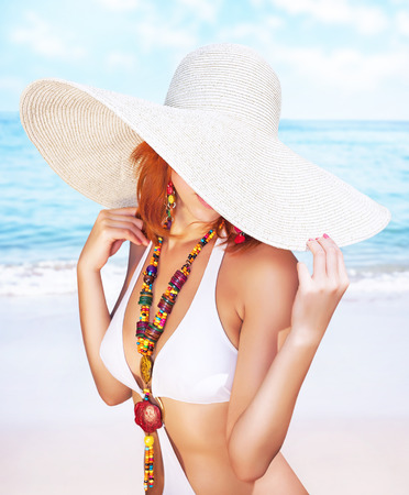 Sexy woman on the beach, fashion model posing on seashore, wearing a big hat, and covers her face, fashionable summer photoshoot