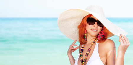 large woman: Portrait of beautiful woman on the beach, wearing stylish sunglasses and big hat, enjoying summer vacation on luxury sea resort, copy space Stock Photo