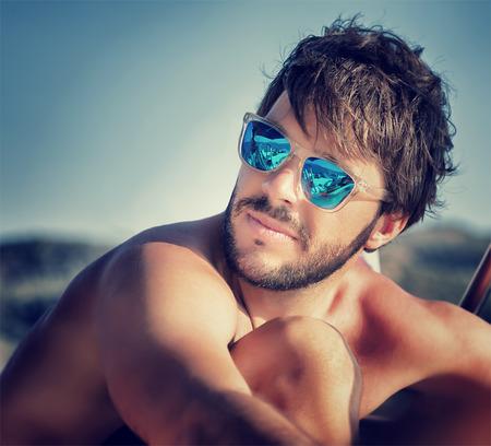 jovem: Retrato do close up do homem considerável na praia na luz do sol suave, vestindo azul óculos de sol à moda, conceito de férias de verão