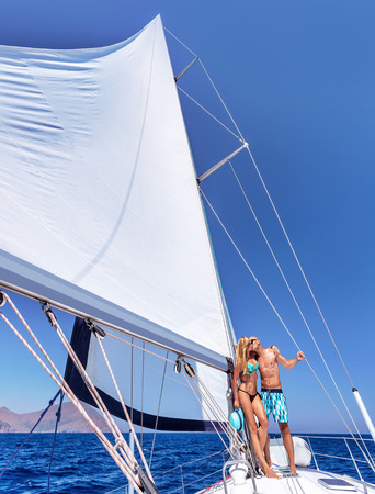 Happy couple in honeymoon vacation in luxury sea cruise, enjoying each other and travel on beautiful sailboat photo