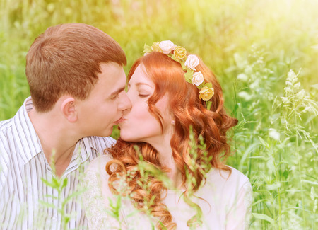 Closeup portrait of beautiful young couple kissing outdoors, spending wedding day in the park, sunny day, love and romance concept photo