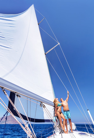 Happy couple in honeymoon vacation in luxury sea cruise, enjoying each other and travel on beautiful sailboat, looking up in the sky photo