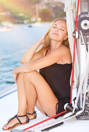 ojos cerrados: Retrato de una bella mujer hermosa con los ojos cerrados, sentado en el yate y disfrutando de la luz brillante del sol, vacaciones de lujo del verano, la libertad y la recreaci�n concepto Foto de archivo