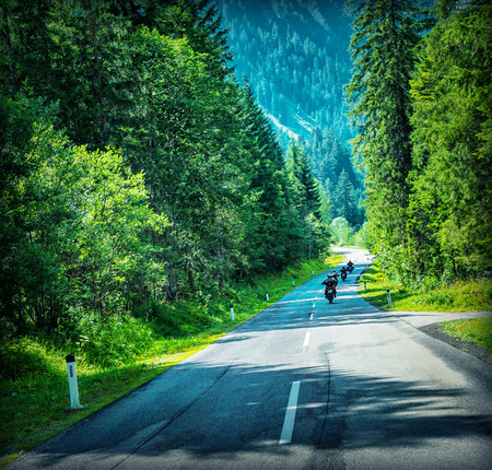 active lifestyle: Motorbikes race, group of sportive people travel on motorcycles in Alpine mountains, enjoying extreme sport, active lifestyle concept