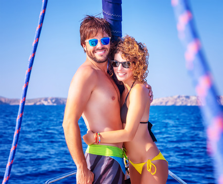Portrait of cheerful young lovers having fun on sailboat traveled along sea, enjoying romantic summer adventure, love and happiness concept photo