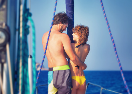 Back side of cheerful young lovers having fun on sailboat traveled along sea, enjoying romantic summer adventure, love and happiness concept photo