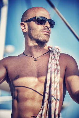 skipper: Fashion portrait of handsome shirtless man standing on the deck of sailboat with rope on shoulders in bright sun lights, sexy sailor, summer vacation and holidays Stock Photo
