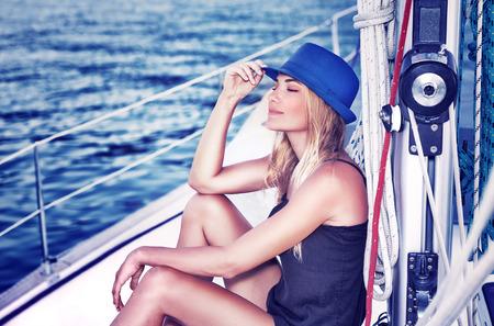 closed eyes: Ontspannen meisje met gesloten ogen van genot zittend op zeilboot, genietend van milde zonlicht, fashion model in luxe zee cruise, de zomer vakantie en reizen Stockfoto