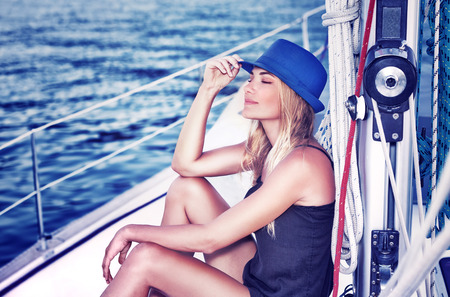 recreation yachts: Relaxed girl with closed eyes of pleasure sitting on sailboat, enjoying mild sunlight, fashion model in luxury sea cruise, summer vacation and travel Stock Photo