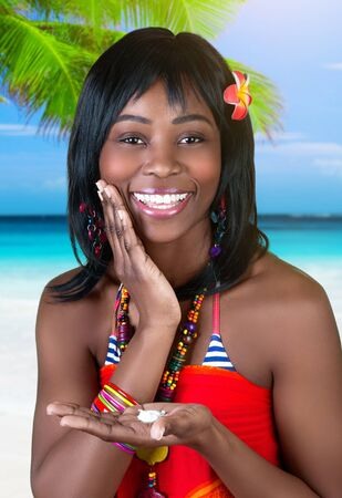 Closeup portrait of beautiful cheerful African female having fun on the beach, using suncream, enjoying happy summer vacation on seashore photo