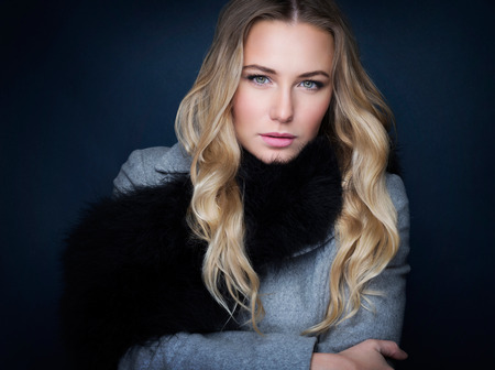 woman black background: Portrait of beautiful gorgeous woman with natural makeup  wearing stylish coat with fur scarf over black background, fashion and vogue concept Stock Photo