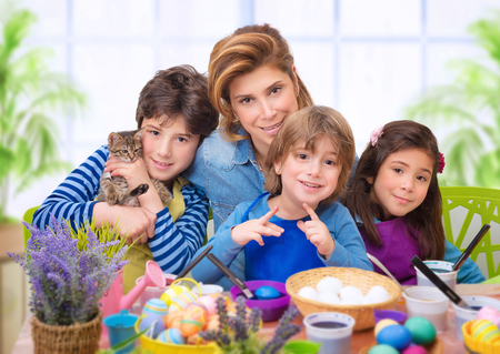 Family portrait in Easter time, creative mother with three cute adorable child coloring eggs, making vibrant colorful traditional food photo