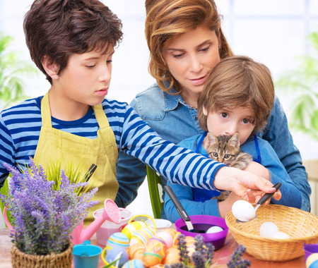 Happy family paint Easter eggs at home, mother with two adorable sons and cute cat make traditional Easter decorative food photo