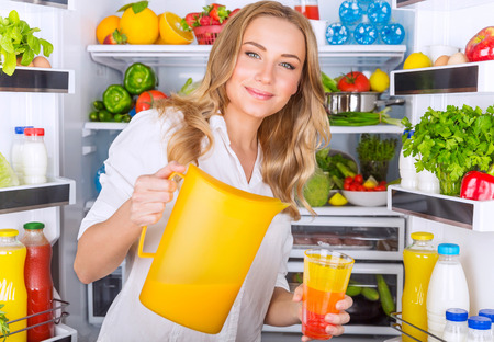 refrigerator with food: Happy woman standing near open refrigerator full of fresh fruits and vegetables and pouring juice in glass, healthy eating concept