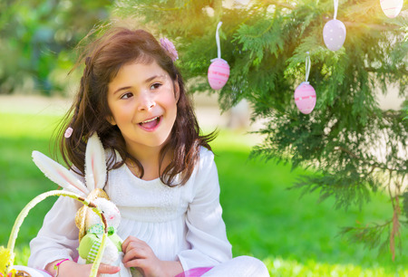 kids having fun: Portrait of nice little girl playing traditional Easter game, happy egg hunting, having fun at spring park in religious holiday Stock Photo